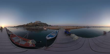mooring : 360 VR video of coastal resort town Nea Kallikratia. View to the quay at sunset. Fishing boats and yachts tied up. Father and son (with model release) on the pier, boy playing with a rope