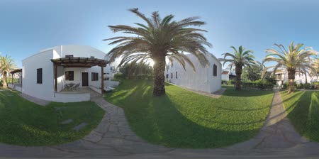ulivo : 360 VR Video. Villas for rent among the olive trees and big palms. Sprinkler system watering green lawns. Cottages for great holidays at Trikorfo Beach resort, Greece