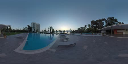 chaise longue : 360 VR video. Hotel and outdoor swimming pool with empty chaise longues on the Mediterranean Sea coast in Antalya, Turkey. Vacation scene at sunset