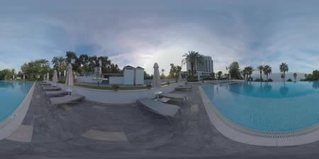 antalya : 360 VR video. Coastal hotel with outdoor pool overlooking sea and mountains. Area with green trees and empty chaise longues. Holiday in Antalya, Turkey