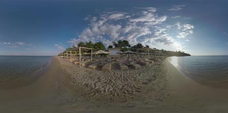 360 VR Video. Vacation scene. Sea skyline and beachline with rows of empty chaise-longues and sun umbrellas. Resort Trikorfo Beach in Greece