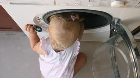 interessado : Curious one year old baby girl is looking into a washing machine trying to find something interesting