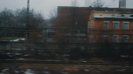 outskirts : Going by train at looking at dull autumn city with industrial facilities, houses and bare trees. Moscow, Russia