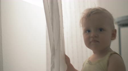 utánzás : Lovely and cheerful one year old child playing with a curtain. Home video imitation