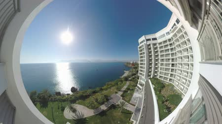 수경 : Wide angle shot of hotel view to the shore of Mediterranean Sea. Scene with green waterfront and bright sun shining and reflecting in water. Vacation in Antalya, Turkey 무비클립
