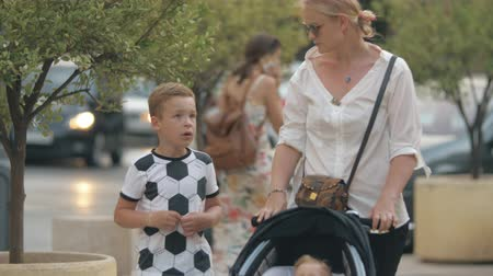 outing : Mother walking with children outside. Son and mum talking with following view to one year old baby in stroller