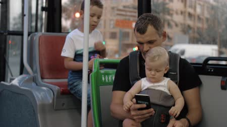 развлекательный : Dad riding in the bus with elder son and one year old baby daughter. Everyone watching fathers smart phone