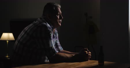 way out : Senior man sitting in dark room with sad and thoughtful look. Bottle of beer is aside on the table. Alcohol is not a way out