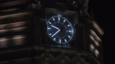 cadran : Close-up shot of illuminated clock on the building of Cybele Palace at night. Madrid, Spain