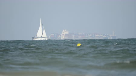 nakládané : White sailboat sailing in wavy sea with loaded container ship in background