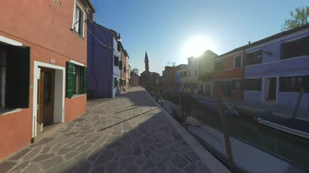 vízpart : Burano scene with colored homes, canal with boats and leaning bell tower of San Martino church. Bright sun shining from behind the house. Italy