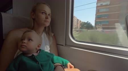dikkatli : Mum with child in the train riding through the city. Woman holding child on the lap and kissing her head. Family travel