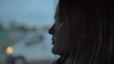 wistful : Close-up shot of a blond woman with sad look in a car. View against the city in the dusk passing by