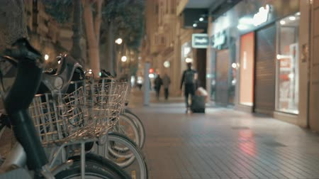 kapalı : Night view of city street with closed stores and some people walking. Bikes for share in foreground Stok Video