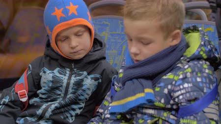автобус : Two kids in overclothes traveling by bus in the evening and watching cartoon on smart phone