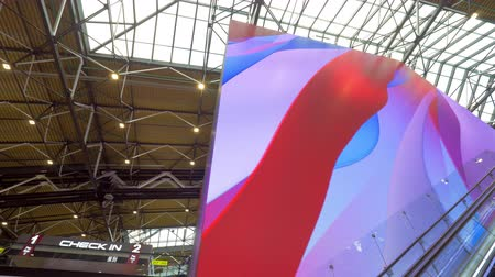 lotnisko : Riding up on the escalator at the airport and looking at digital cube screen displaying colorful waves Wideo