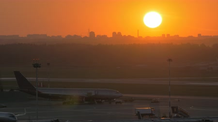 being prepared : View of the airport at sunset. Passenger airplane being prepared for the flight and loaded