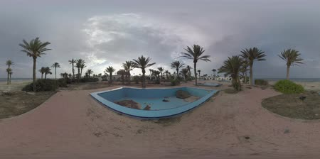 törmelék : 360 VR video. Sea view and waterfront with abandoned resort. Desolated area with empty pools and decayed shabby buildings among the palms Stock mozgókép
