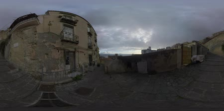 donuk : 360 VR video. Naples street view, Italy. Paved path leading up and down along the shabby and decayed street brick walls and the worn facade of old house