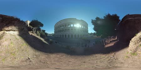 flavian : 360 VR video. Rome cityscape with the Colosseum and Piazza del Colosseo, Italy. Visitors gathering near the major ancient landmark and touristic buses arriving. View in sunny winter morning