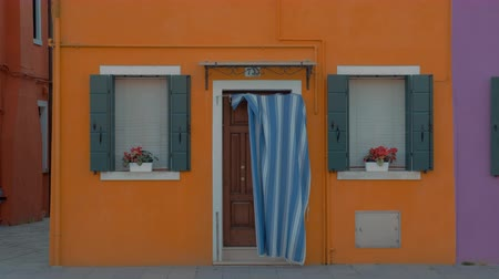burano : A bright yellow facade of a small house in Burano, Italy. Blue window shutters are opened and bright pink flowers are decorating the window sills. A stripped piece of fabric is covering the entrance door