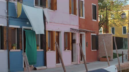 redőnyök : Colorful residential facades of italian Burano. Small houses are blue, pink, yellow, white and red. Window shutters are opened and bed linen is slowly swaying in the wind. Green tree branches are seen between the houses and warm sunrays are coloring brigh