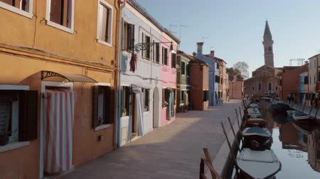 burano : A beautiful view of italian Burano on a bright sunny day. Small colorful buildings along the paved embankment, empty boats on glossy water. A stone tower of an ancient church is rising on the background against the blue sky and some people are crossing th Stock Footage