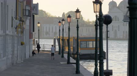 lamppost : A Venice paved embankment with beautiful lampposts on it, two people and a dog. The calm water is sparklings in warm sunrays and a boat is swaying on it close to the embankment