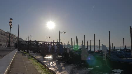 lamppost : A slowmotion of covered gondolas swaying on a pier close to the paved Venice embankment. Beautiful lampposts are standing along it. The sun is shining in the middle of the blue sky