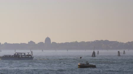 моторная лодка : A powerboat is crossing the sparkling water against the misty Venice view. The sky is blue and everything is lightened by a warm evening sun. A lonely bird is flying close to the water
