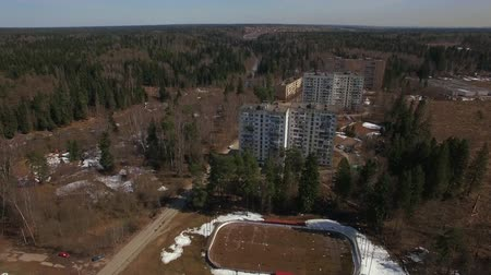 arborizado : An aerial view of residential multi storey buildings in a wooded area on a bright sunny day. Green spruces and blue sky are adding color to the ordinary scenery. Snow is partially covering the ground