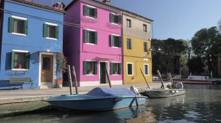 burano : Three colorful facades of small houses of italian Burano on a beautiful sunny day. Window shutters are opened and bright pink flowers are decorating some window sills. Small boats are slowly jiggling on sparkling water of the canal