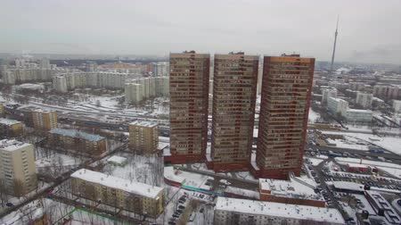 no traffic : An aerial view of Moscow residential area with three multi storey buildings rising above the urban surroundings. Rooftops and the ground are covered in snow. The grey sky and leafless trees are creating the winter mood Stock Footage
