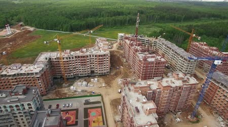 ileri : An aerial view of a construction site near the green forest. A big residential complex is under the construction with several cranes around it. Some finished buildings can be seen next to the construction site. A beautiful green forest is on the backgroun Stok Video