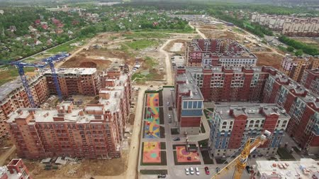 arborizado : An aerial view of a construction site of modern residential buildings. Some of them are looking finished with green lawns, parked cars and playgrounds. And some have construction cranes next to them. There is a large wooded area on the background with sma Vídeos
