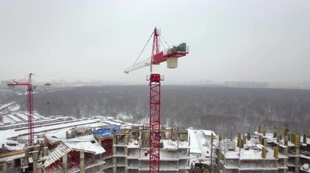 preenchido : A working construction crane moving above the building construction area. Snow is covering the ground and rooftops. Another crane is located a bit further. A background scenery is filled with trees and misty faraway residential buildings