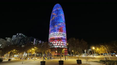 nocturnal : Timelapse night shot of people and transport traffic in the street with Torre Agbar and its colourful illumination. Barcelona, Spain