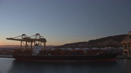tersane : Timelapse shot of loading container ship with cargo at the industrial port. Cranes working from day to night. Barcelona, Spain Stok Video