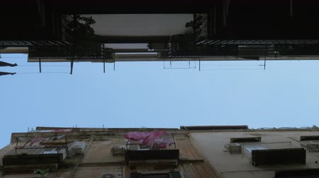 roto : Bottom view of the aged buildings and sky. Linen hanging on the balconies and waving in the wind. Naples, Italy Stock Footage
