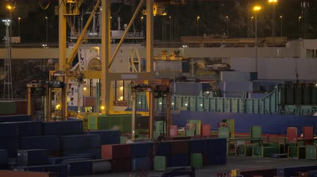 dockyard : Evening view of industrial port with machines transporting containers and cranes loading cargo ship