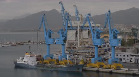tersane : Industrial port with container cranes and moored cargo ship, distant coastal city and mountains in background Stok Video