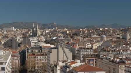 scény : Panoramic view of Marseille, France. City architecture with Saint Vincent de Paul Church and green hills in background Dostupné videozáznamy