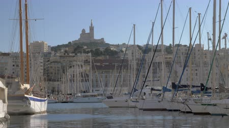 marseille : Scene with moored yachts and quayside houses in Old Vieux Port and Notre-Dame de la Garde on the hill. Marseille, France