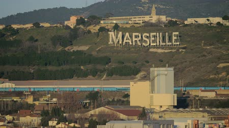 naam : Marseille large sign on green hill. City view with train passing by and houses in foreground, France Stockvideo