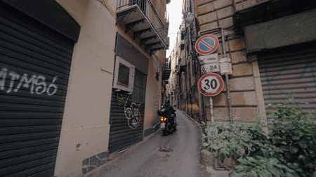 Сицилия : Slow motion shot of unidentified motorcyclist driving through the narrow alleyway in Palermo, Italy