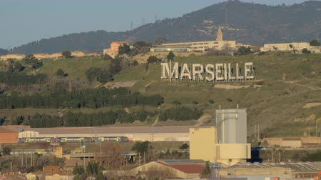 marseille : Suburb Marseille hills with huge letters MARSEILLE, a railway and a train, moving along it Stock Footage