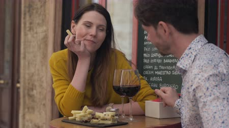 spaanse wijn : A young couple sitting at a small table of cafe terrace, drinking red wine from big glasses and trying cheese from a cheese plate Stockvideo