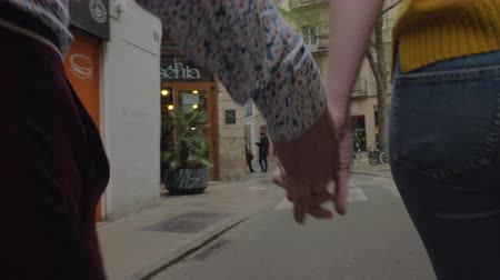 handen ineen : A street in Valencia, we see it through the joined hands of a walking young couple