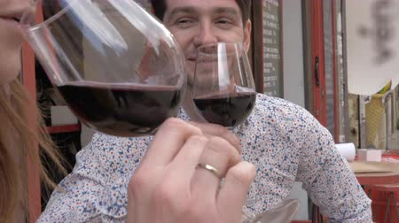 spaanse wijn : A young man drinking red wine with his fiance at a cafe terrace