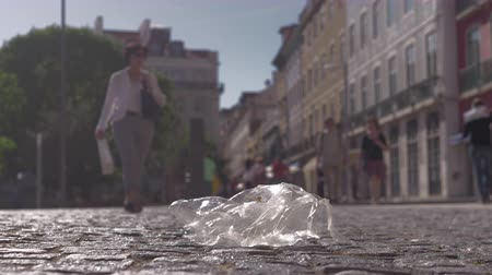 passerby : A transparent plastic packet, being moved by wind on a city pavement Stock Footage
